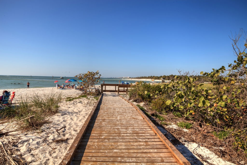 Boardwalk across the white sand beach of Delnor-Wiggins Pass State Park with a blue sky above in Naples, Florida.