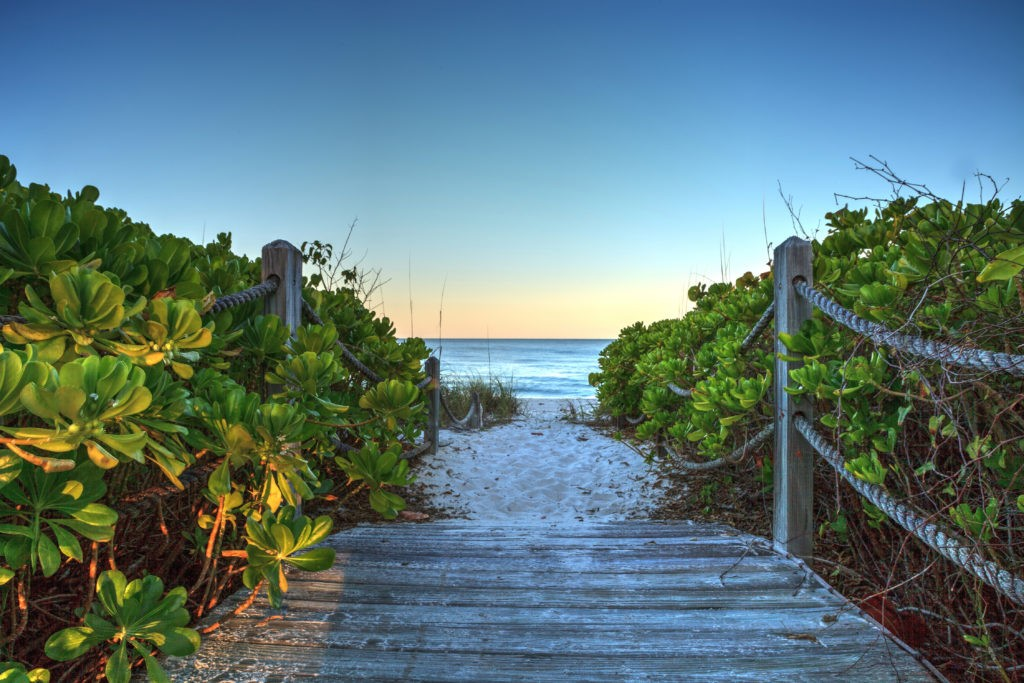 Boardwalk leading down to the white sand of Vanderbilt Beach at sunrise in Naples, Florida.