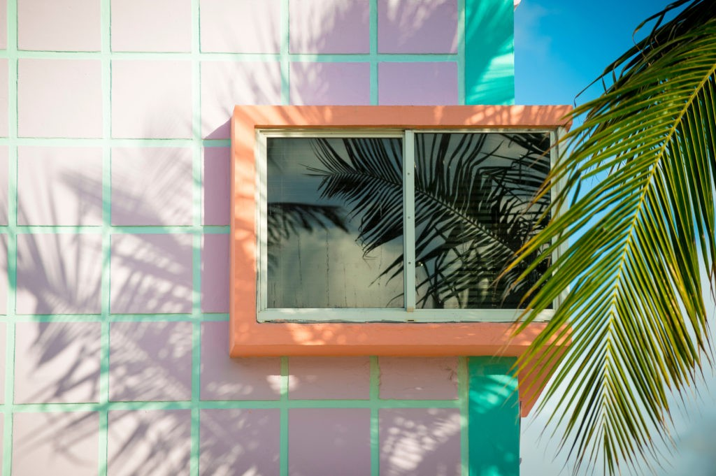 Detail close-up of typical colorful Art Deco architecture with tropical palm tree shadows in South Beach, Miami, Florida
