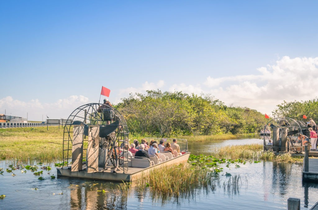 EVERGLADES, USA - NOVEMBER 30, 2013: group of international tourists leaving from the airboat pier. The Everglades are a natural region of wetlands in the southern portion of the US state of Florida.