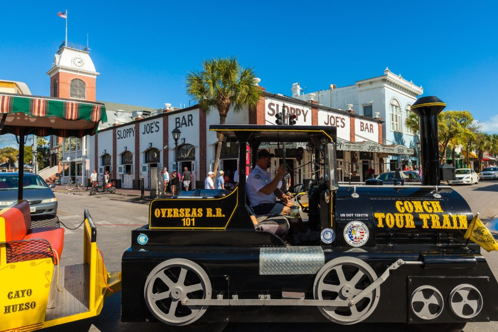 Key West, Florida USA - March 3, 2015: The historic Sloppy Joe's Bar on Duval Street in downtown Key West with the Conch Train.