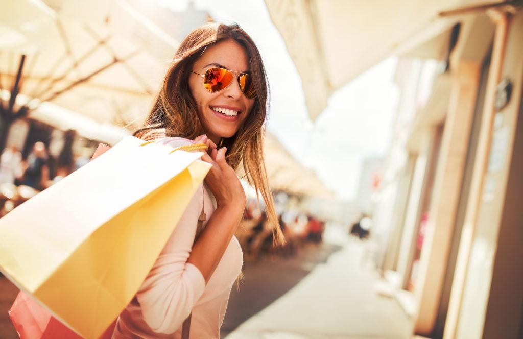 Kobieta na zakupach. Szczęśliwa kobieta z torebkami na zakupy. Konsumeryzm, zakupy, koncepcja stylu życia