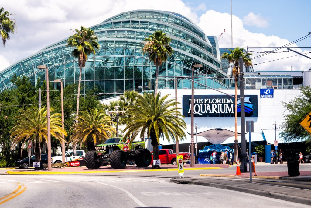 Tampa, USA - April 27, 2018: Downtown city in Florida and sign on modern building exterior for aquarium with street road and palm trees