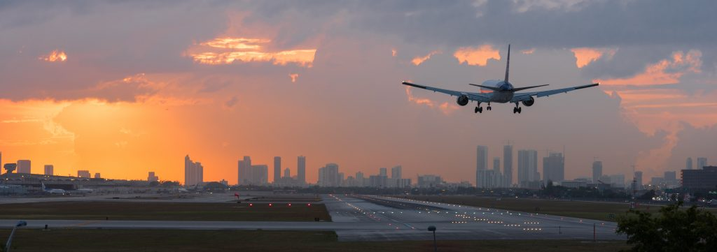 MIAMI, FLORIDA - APRIL 2018: Airplane landing at Miami International Airport with Downtown Miami skyline in the background.